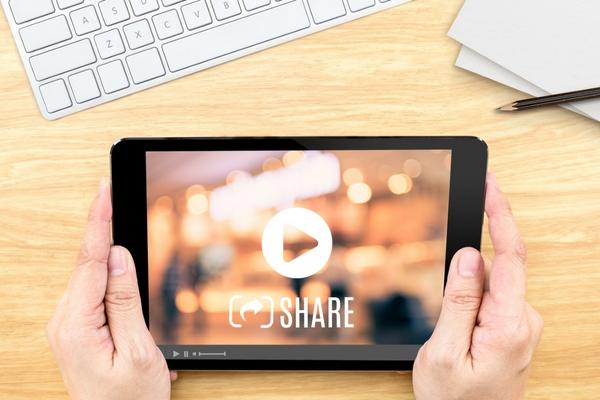 Eine Person hält ein Tablet, auf dem ein Video und das Wort 'Teilen' zu sehen ist.