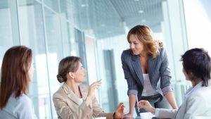 Eine Gruppe von vier Mitarbeiterinnen an einem Tisch diskutiert eine Projektmanagementstrategie.