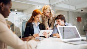 Drei Kollegen sitzen um einen Tabletcomputer herum und beraten sich zu einer Projektmanagementstrategie.