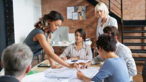 Sechs Kollegen an einem Konferenztisch voller ausgedruckter Diagramme und Daten diskutiert das weitere Vorgehen.