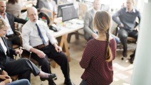 Eine junge Frau in einem geschäftigen Büro hält stehend einen Vortrag vor ihrem Team.
