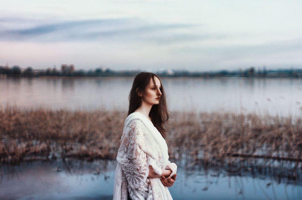 A woman walking in a marsh.