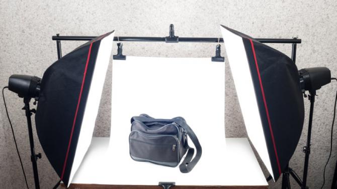 Eine lederne Tasche steht gut ausgeleuchtet zwischen zwei Fotoscheinwerfern und vor einem weißen Fotohintergrund.