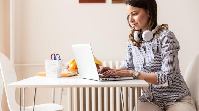Eine junge Frau sitzt an einem Tisch und arbeitet auf einem Laptop, während um ihren Hals Kopfhörer hängen.