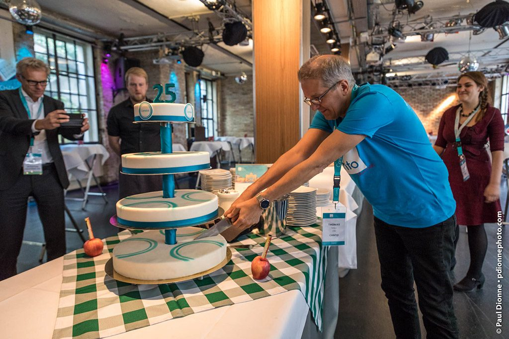 Picture of a man cutting a cake, while other persons look on and take pictures.