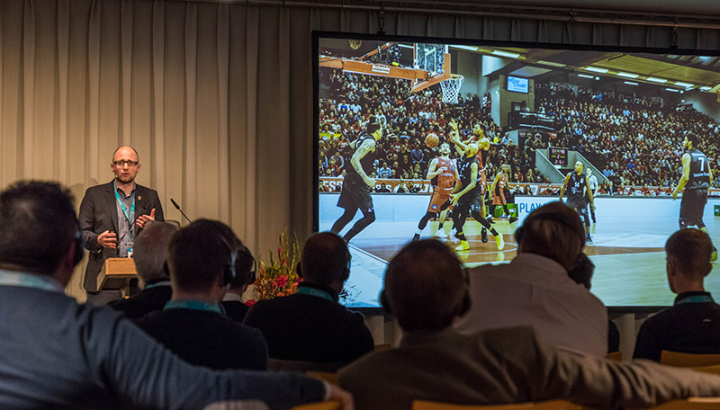 A person in front of an audience is giving a talk while showing a large projected image of a basketball game.