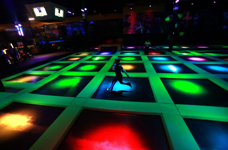 Glowi9ng lights on main court of trampoline park with a running boy.