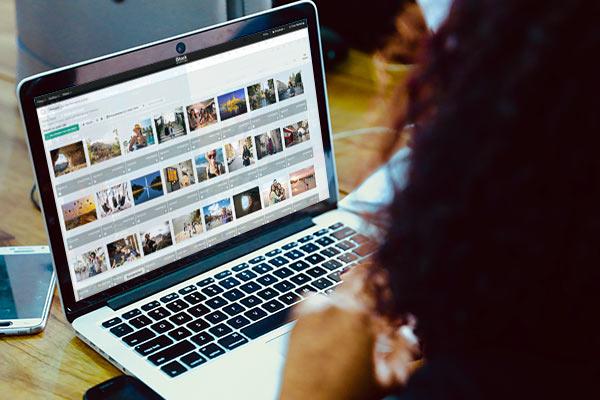 Eine Person betrachtet Stockfotos auf einem Laptop.
