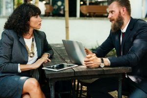 Ein Mann und eine Frau sitzen mit einem Laptop und einem Tablet an einem Tisch im Freien und besprechen etwas.