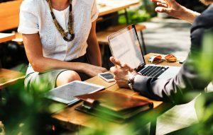 Ein Mann und eine Frau diskutieren an einem Tisch sitzend über Dinge, die auf einem Laptop zu sehen sind.