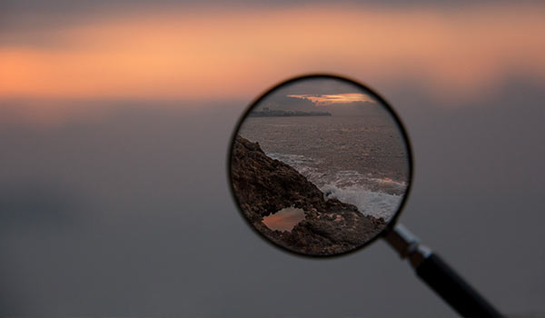 A magnifying glass in focus on mountains and the sea.