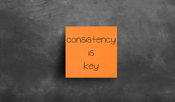 A sticky note that says 'consistency is key'.