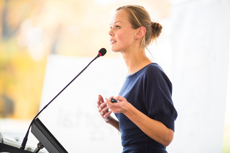 A woman is giving a speech in front of a microphone.