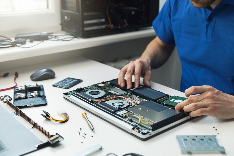A man is adjusting the hardware components of a partially disassembled laptop on a table in front of him.
