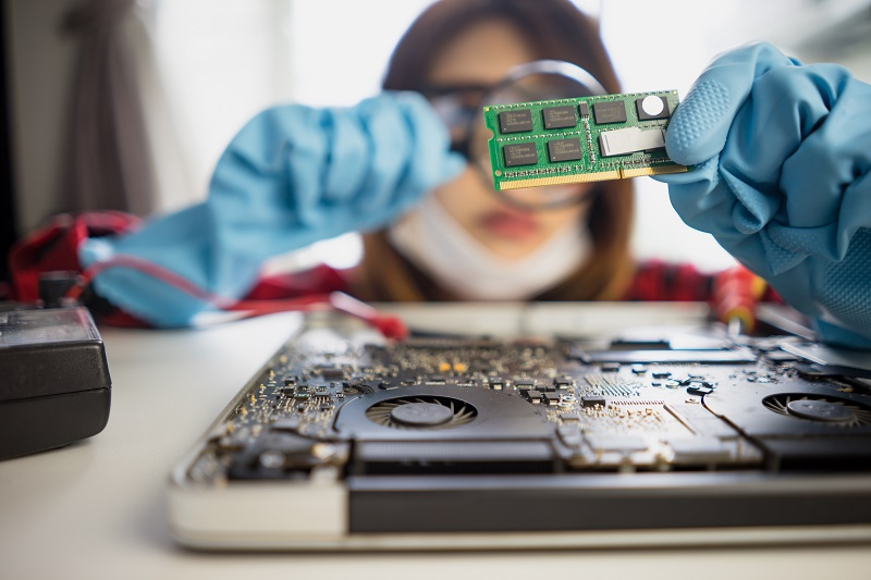 A female computer technician is inspecting a printed circuit board with some processor chips with the help of a magnifying glass.