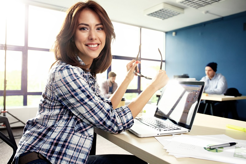A woman smiles at the camera as she works at her office on a laptop.
