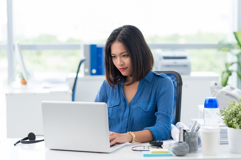 A young woman at a modern office uses a laptop on a desk.