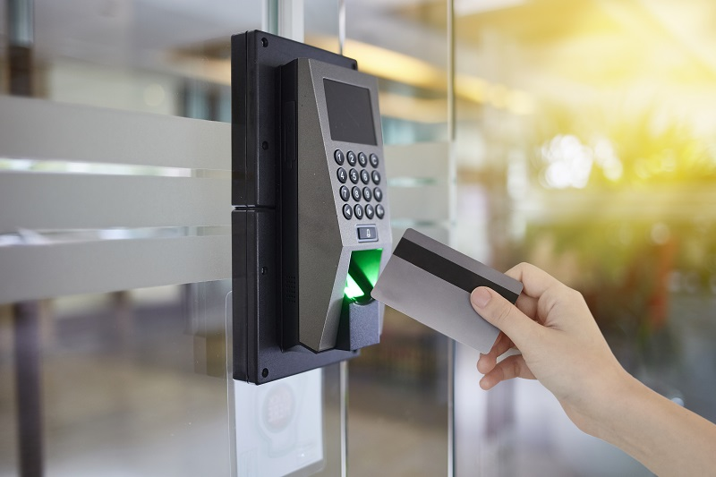 A hand uses a security card on a locked keypad.