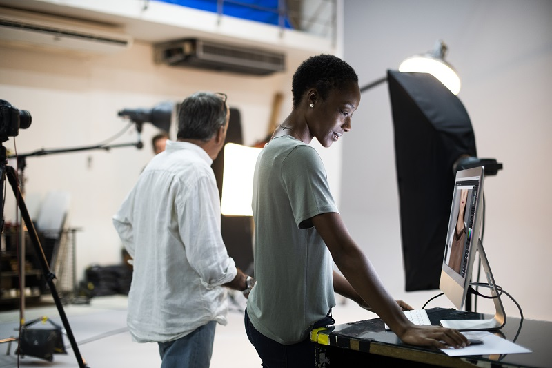 A young woman stands next to a man, editing film from video cameras next to them.