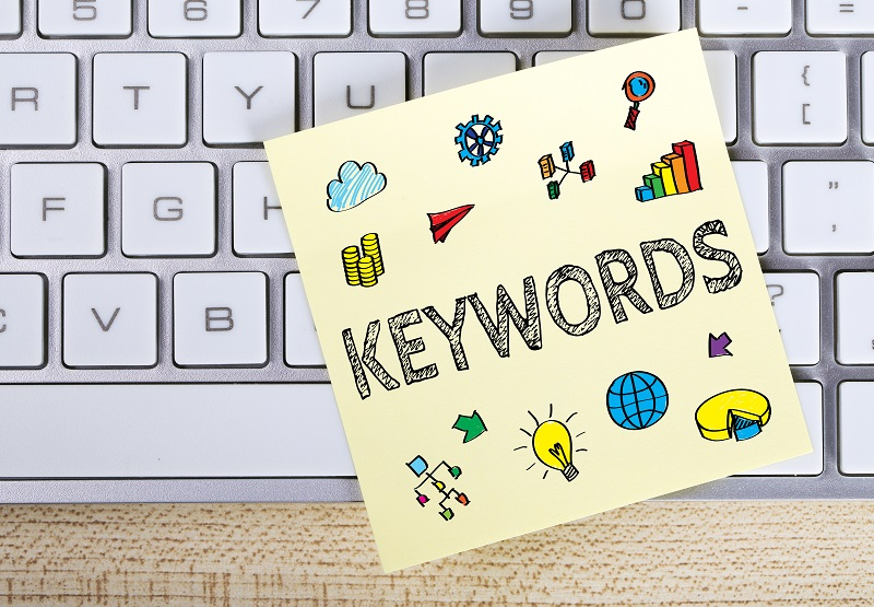 A picture of a keyboard with a sticky note on it that says 'keywords'.