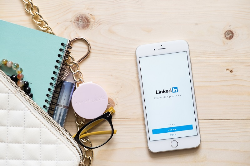 A picture of a desk with a mobile phone showing the Linkedin page.