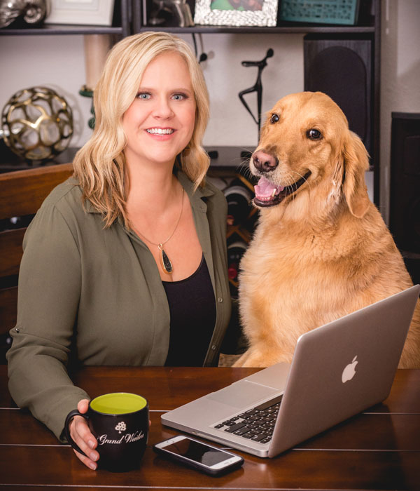 Carin Martens sitting at a table with a laptop and a large dog next to her.