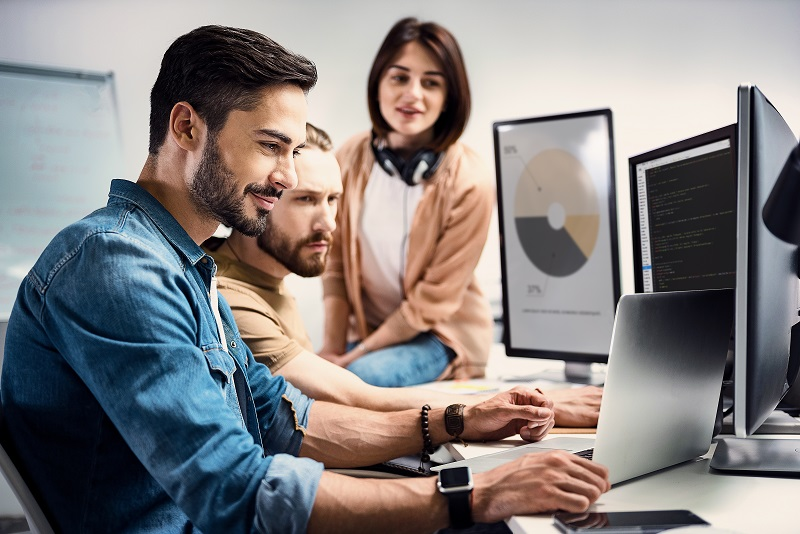 Two male and one female worker using different computers for graphics.