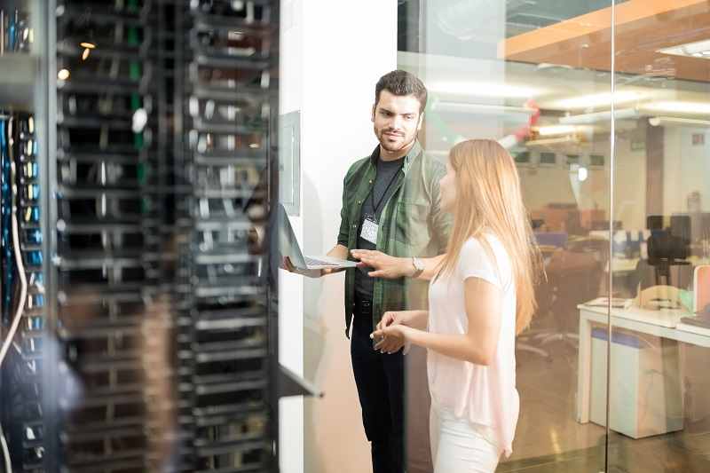 A man and woman coworkers review a data server.