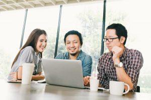 Drei Mitarbeiter arbeiten mit Freude an einem Laptop.
