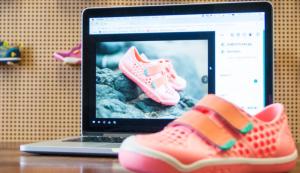 Ein Paar Kinderschuhe neben einem Laptop, der dasselbe Paar Kinderschuhe auf einer Webseite zeigt.