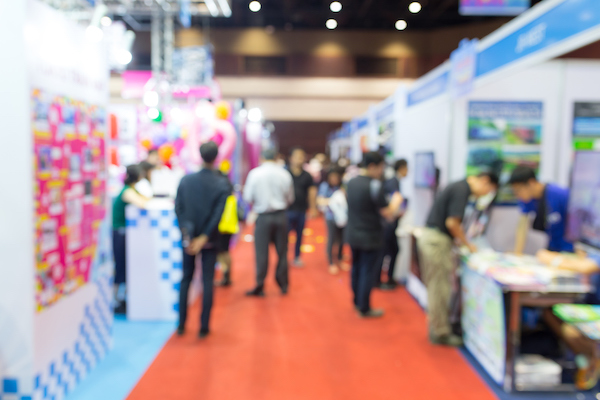 A deliberately blurred photograph of a convention bustling with people.