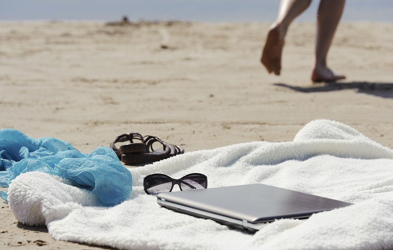 A woman leaves her laptop unattended at the beach.