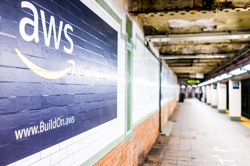 A picture of the Amazon AWS logo painted on a brick wall.