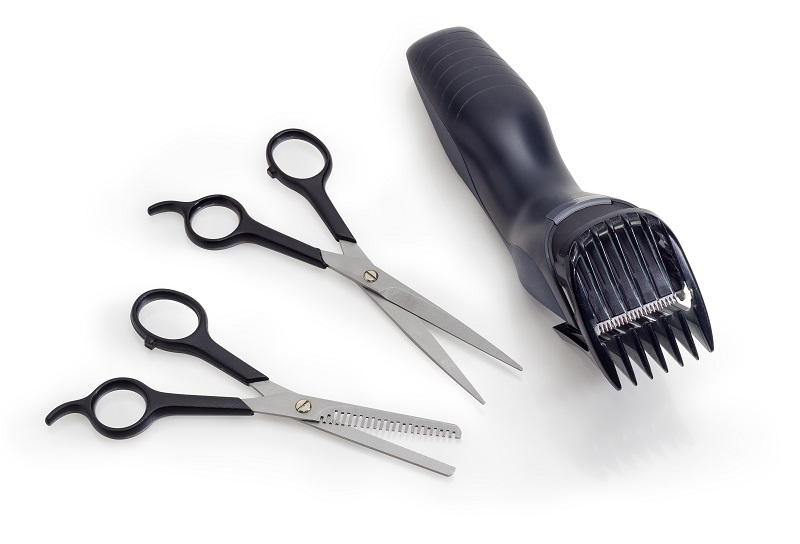 A pair of electric clippers with two small scissors.