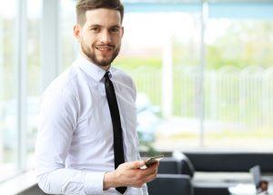 Ein junger Geschäftsmann lächelt selbstbewusst in die Kamera, während er ein Smartphone hält.