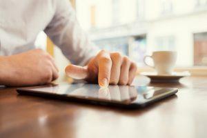 Ein Mann, der an einem Tisch sitzt, arbeitet mit der Fingerspitze auf dem Touchscreen des vor ihm liegenden Tablets.