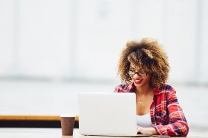 Eine junge Frau arbeitet voller Begeisterung an ihrem Laptop.