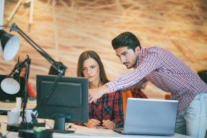 Ein Mann zeigt auf etwas auf einem Computerbildschirm, während seine Arbeitskollegin es mit dem Laptop vor ihr vergleicht.