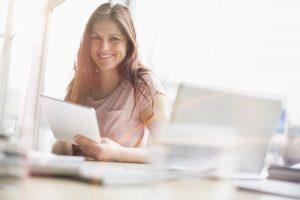 Eine junge Frau lächelt die Kamera an, hält ein Tablett und sitzt neben einem Laptop in einem Büro.