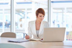 Eine junge Frau konzentriert sich auf ihre Arbeit, während sie zeitgleich auf ihren Laptop schaut und sich Notizen auf ihrem Notizblock macht.