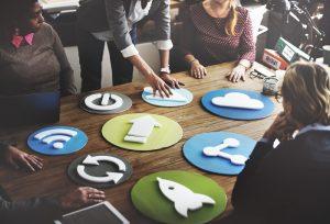 Eine Gruppe von Mitarbeitern steht diskutierend an einem Tisch, auf dem verschiedene ikonische Symbole als Plastikformen ausgelegt sind, unter anderem die Symbole für WLAN, Cloud, Seite neu laden und Teilen per Social Media.