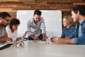 Fünf Mitarbeiter definieren gemeinsam eine Strategie, wobei einer von ihnen sie auf einem Papier auf dem Tisch vor sich notiert.