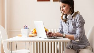 Eine junge Frau mit Kopfhörern sitzt an einem Küchentisch, auf dem sich eine Obstschale, ein Buch und Stifte befinden, und arbeitet mit ihrem Laptop.
