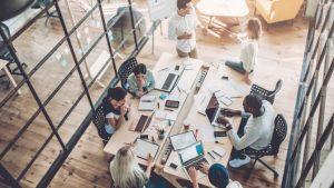 Eine Gruppe von Mitarbeitern in einem modernen Büro hat sich um einen Tisch voller Laptops, Papiere und Diagramme versammelt und berät in einer lebhaften Diskussion miteinander.