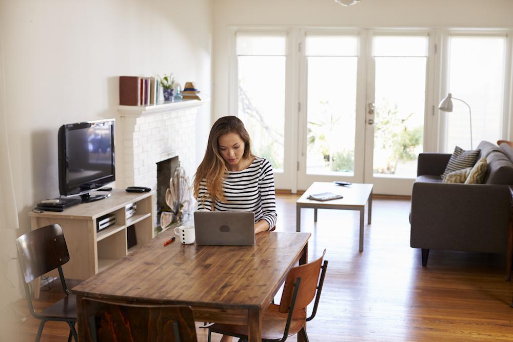 Eine junge Frau sitzt in einem modernen Wohnzimmer an einem braunen Holztisch und arbeitet mit ihrem Laptop.
