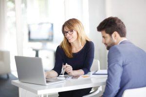Eine Frau, die einem Mann im Anzug an einem Tisch sitzend Informationen auf einem Laptop zeigt.