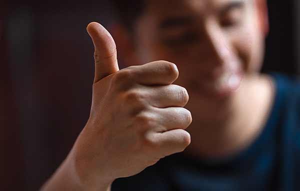 Eine Person signalisiert mit dem Daumen nach oben ihre Zustimmung.