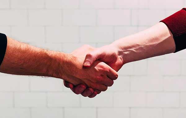 Zwei Personen schütteln sich die Hände.