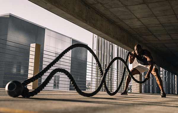 Ein Mann trainiert an den Übungsseilen.