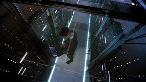 Ein Mann überprüft die Server in einem Rechenzentrum mit Hilfe seines Laptops.